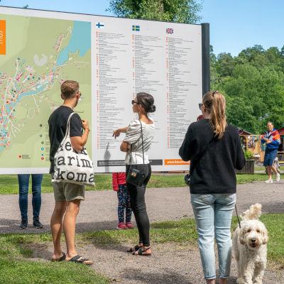 Besökare läser en informationsskylt i Fiskars bruk.