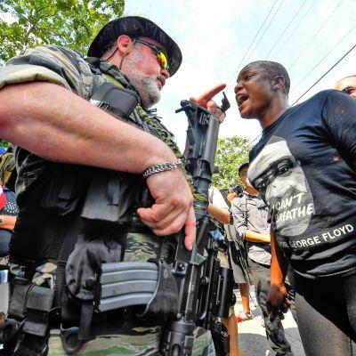 Raskaasti aseistautunut militian jäsen ja musta mies vastakkain miielenosoituksen aikana.