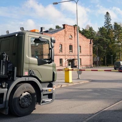 Ett större fordon står och väntar på att få köra in på ett garnisonsområde. Trafikljuset lyser rött och en bom avgränsar vägen.