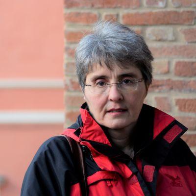 Medelålders kvinna utomhus med röd tegelvägg i bakgrunden. Gymnasieläraren Giuseppina Tobaldi väntar på att få undervisa i klassrummet.