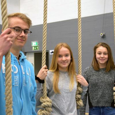 Jacob Österman, Malin Alén och Ida Simonen står vid några gymnastikrep som hänger ner från taket.