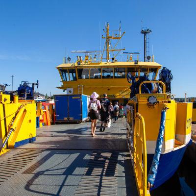 Matkustajia kävelee Yhteysalus Otavan kyytiin Kuusisen satamassa.