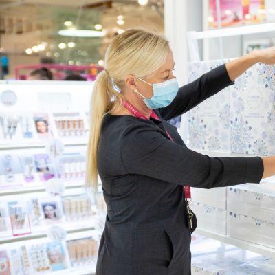 Lumenen konsulentti hyllyttää tuotteita myymälässä.