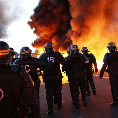 Polisen försöker röja en brinnande barrikad vid ett oljeraffinaderi i Douchy-les-Mines i norra Frankrike.