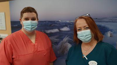 Två hälsovårdare med munskydd framför en tavla med vinterlandskap, Camilla Rautanen i röd sköterskedräkt och Carola Silander-Lehtinen i blå sköterskedräkt.