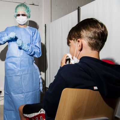 Kuvassa lähihoitaja Viitanen ohjeistaa 10-vuotiasta poikaa koronavirustestin tekemiseksi. Ensin niistetään nenä tyhjäksi.
