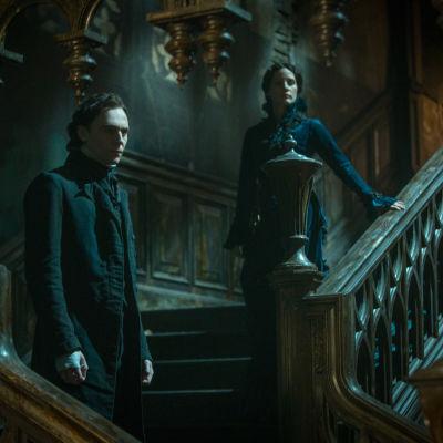 Tom Hiddleston och Jessica Chastain står i bred trappa i skräckens boning.