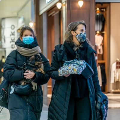 Kaksi nuorta naista kävelee kauppakeskuksessa hengityssuojaimet kasvoillaan. Toisella on sylissään mäyräkoira, toisella lahjapaketti.