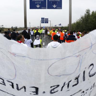 Demonstranter blockar vägen i Calais och kräver att flyktinglägret i staden ska stängas.