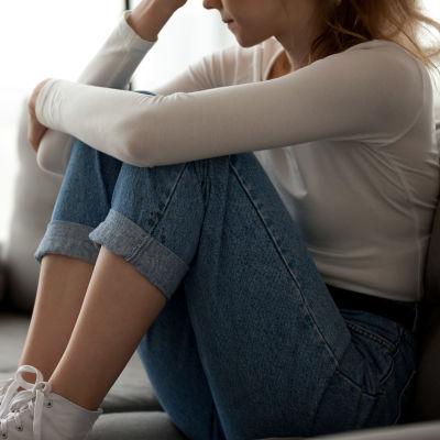 Anonym kvinna ensam på soffa.