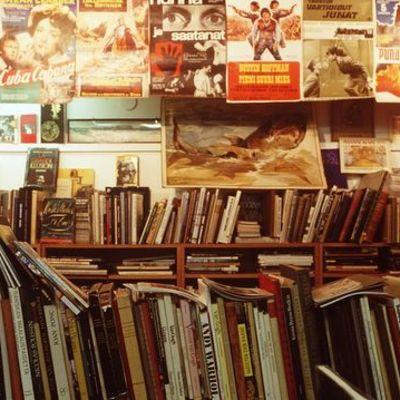 Kirjoja hyllyssä ja julisteita seinällä
