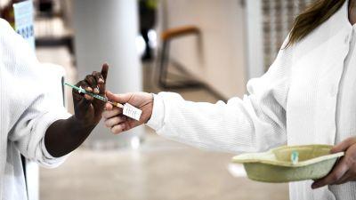 En vårdare i färd med att ge över en spruta med coronavaccin till en annan vårdare.