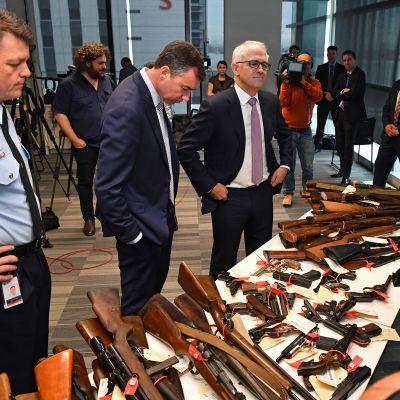 Justitieminister Michael Keenan och premiärminister Malcolm Turnbull ser på en del av de över 50 000 vapen som polisen samlade in