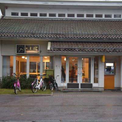 Ett före detta bankhus i Tenala. Man kan se några barn inne. Utanför finns några cyklar.