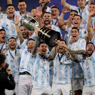 Lionel Messi lyfter pokal med lagkamrater.