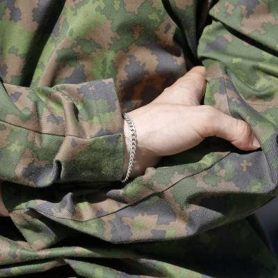 En beväring som står med armarna i kors.