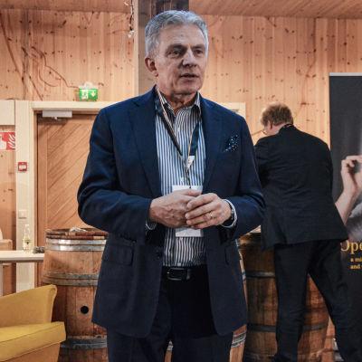 En man i övre medelåldern iklädd skjorta och kavaj håller tal.
