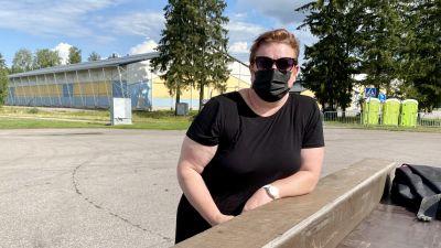 En kvinna med solglasögon och munskydd lutar sig mot någonting och tittar in mot kameran.