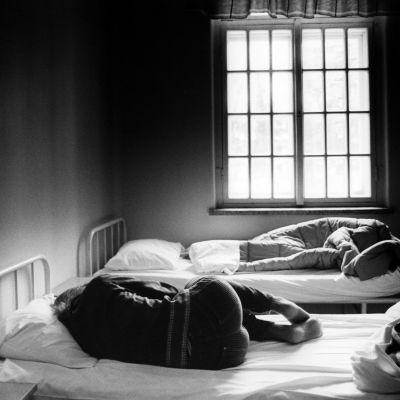 Nuori nainen (tyttö) makaa selin mielisairaalan sängyssä.