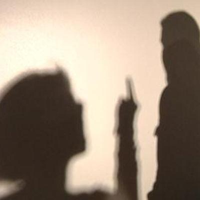 Skugga av kvinna som visar mittfingret åt man.