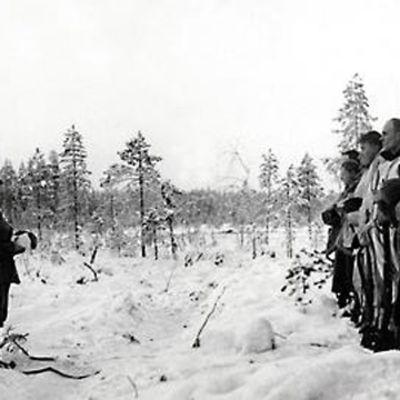 Soldater under vinterkriget står uppställda på led med huvudbonaderna i händerna.