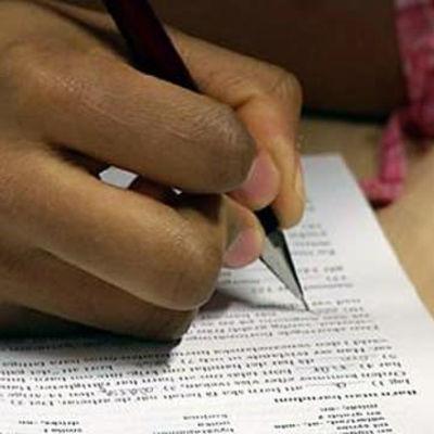 Hand skriver prov på papper.