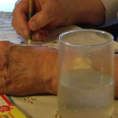 två äldre händer, sitter och löser korsord, ett vattenglas bredvid.
