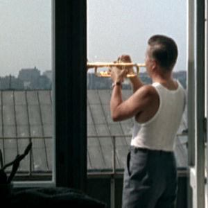 Ossi Runne soittaa trumpettia parvekkeella elokuvassa Lauantaileikit (1963)