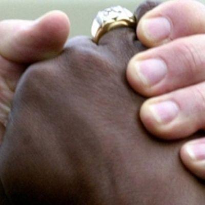 Två händer, en svart och en vit, som håller om varandra.