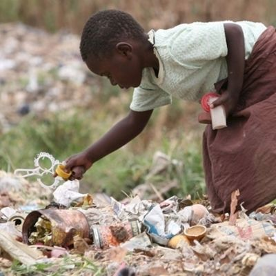 Liten flicka i Zimbabwe plockar skräp.