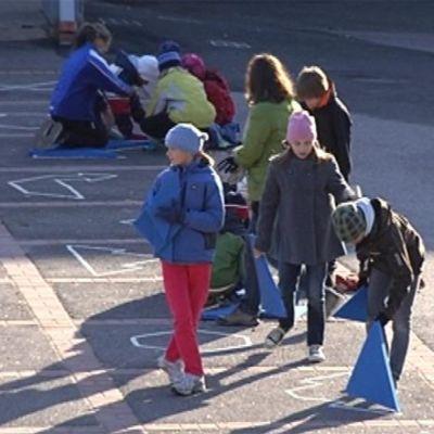 Elever lägger tangram på skolgården