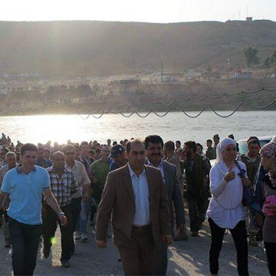 Syriska flyktingar går över gränsen till irakiska Kurdistan i Duhuk