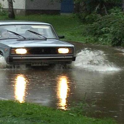 Auto ajaa tielle nousseessa tulvavedessä