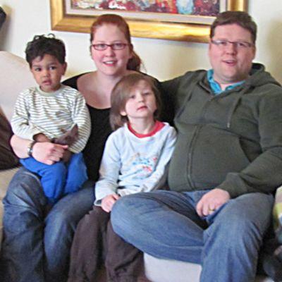 Sallisen perheeen pienimmät lapset isän ja äidin kainalossa.