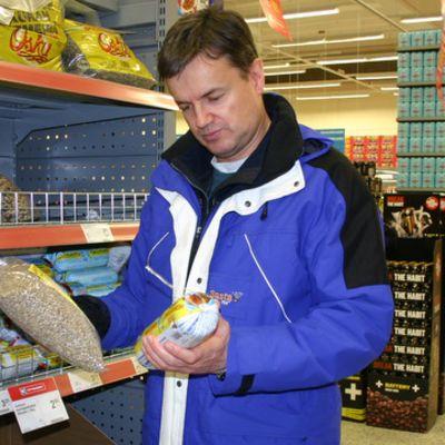 Mies tutkailee linnunruokia kaupassa
