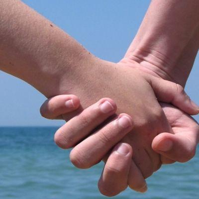 Två människor håller varandra i handen.