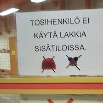 Atalan koulun kyltissä lukee, että tosihenkilö ei käytä lakkia sisätiloissa.