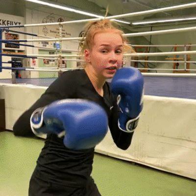 Nainen iskee nyrkkeilyhanskat kädessä kohti kameraa