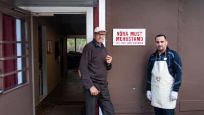 Två män står invid en öppen dörr, på väggen hänger en reklamskylt