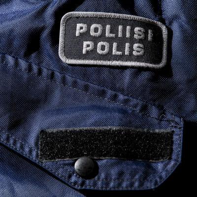 Yksityiskohta poliisin sinisessä virkapuvussa.