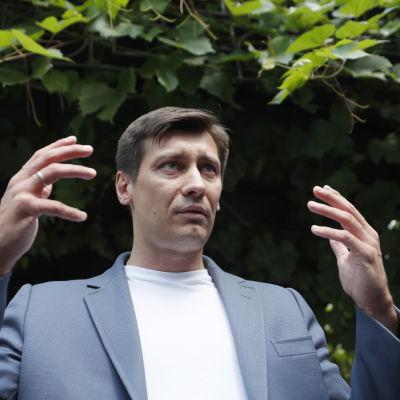 Ett porträtt på Dmitrij Gudkov, i bakgrunden buskar.