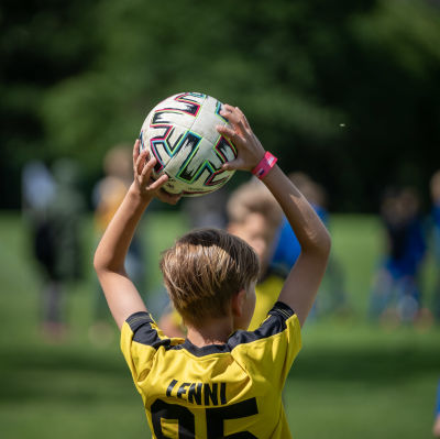 Ett barn med kort hår och fotbollströja håller en fotboll över huvudet.