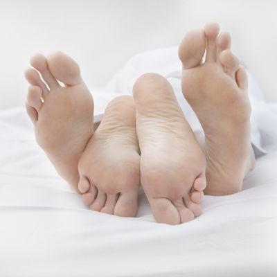 Fötter i säng.