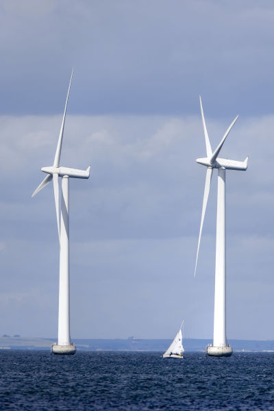 Två stora vindmöllor till havs, med en liten segelbåt mellan sig.