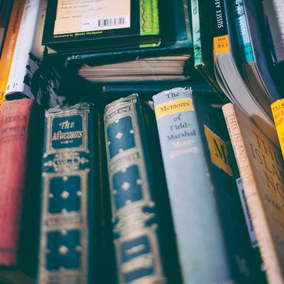 Flera böcker med ryggen mot betraktaren.
