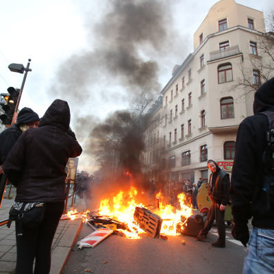Vänsteranhängare står vid en brinnande barrikad efter våldsam motprotest mot nynazistisk demonstration.
