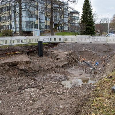 En stor grop i ändan av Tullbron i Lovisa, omringad av ett stängsel.