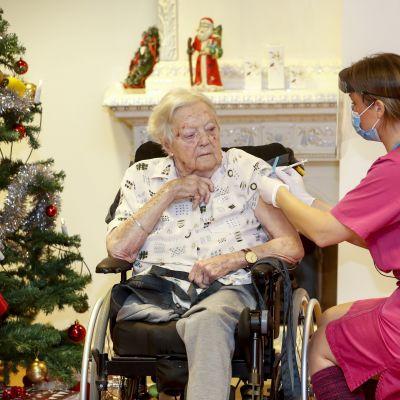 En äldre dam i rullstol vaccineras för covid-19. Bilden är tagen i Mjölby i Sverige.