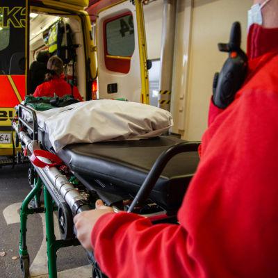 Ensihoitajat lastaamassa tyhjiä paareja ambulanssiin.