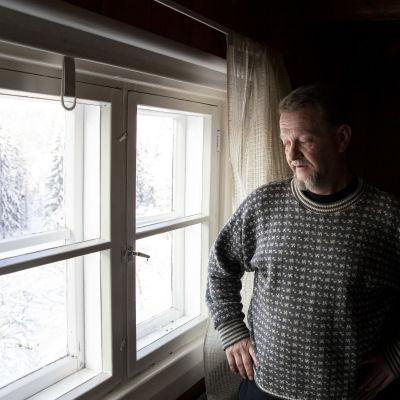 Timo Ruuska katsomassa ikkunasta ulos.